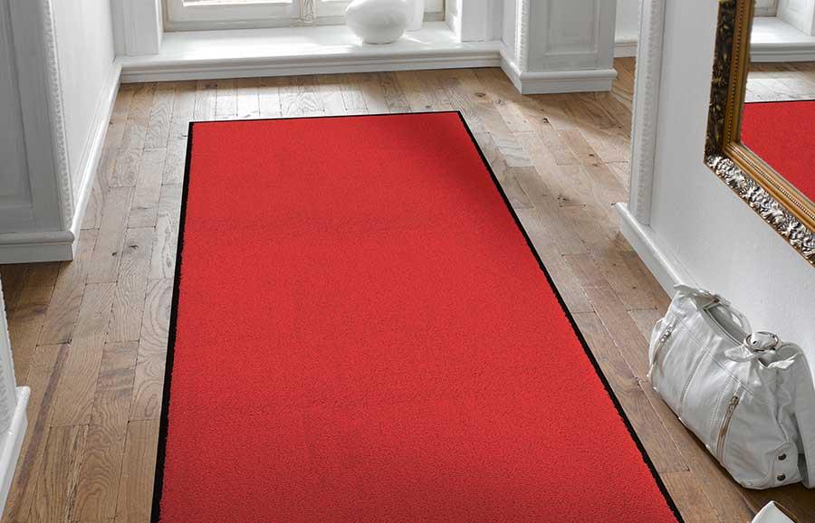Een vloerkleed in de hal op een houten vloer, dat fungeert als rode loper