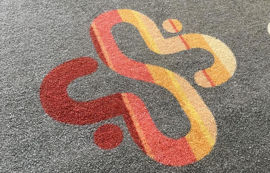 Een vloermat met logo in detail. Onze vloermatten worden tot in de kern van de vezels gekleurd.